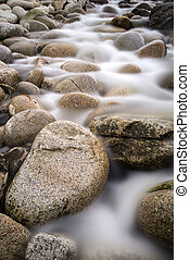 Stream flows over water worn round rocks