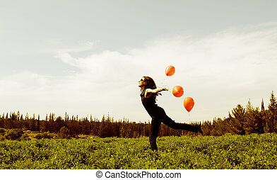 Young woman with red balloons on the field