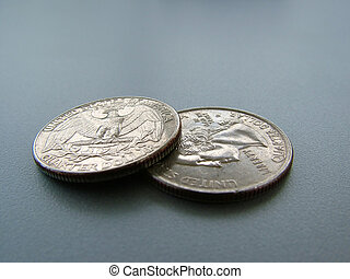 Coins on a gray table - Two quartar-dollar coins flipped on...