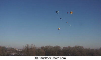 Many hot air balloons flying over forest