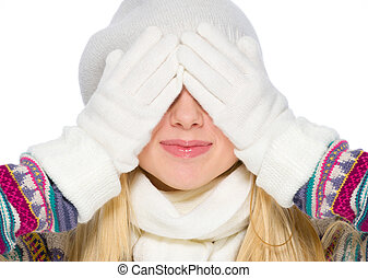 Girl in winter clothes covering eyes with hands