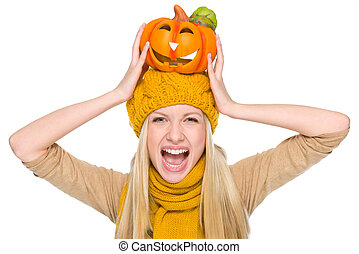 Girl in hat and scarf with jack-o-lantern on head