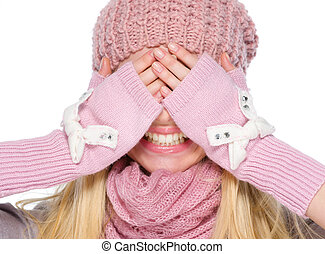 Portrait of happy girl in winter clothes covering eyes with hands