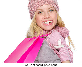 Smiling girl in winter clothes with shopping bags