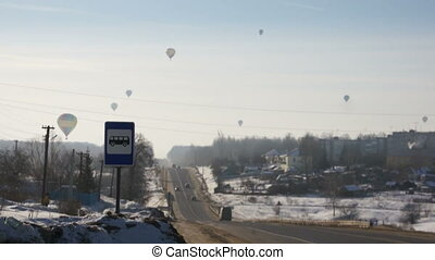 Hot air balloons flying over urban road