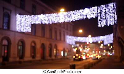 Movement of cars down the street with festive illumination, bokeh