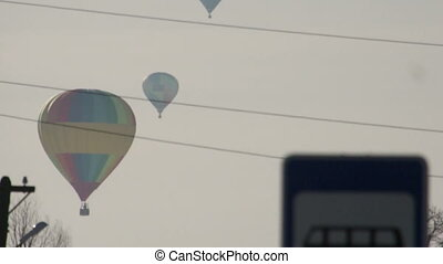 Colorful hot air balloons flying over road sign, close-up