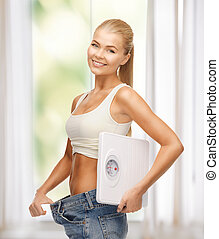 woman showing big pants and holding scales - sporty woman...