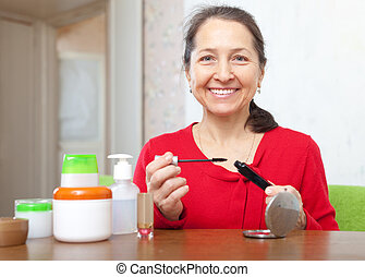 mature woman puts mascara on - Smiling happy mature woman...