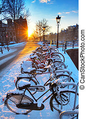 Amsterdam snow bicycles - Sunrise over the canal streets of...