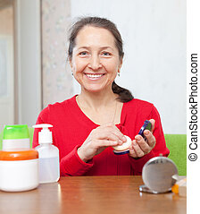 mature woman puts facepowder - Happy mature woman in red...