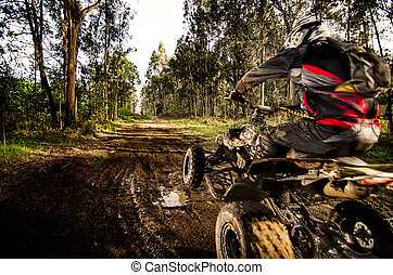 Quad rider jumping on a muddy forest trail.