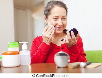 Happy mature woman in red puts facepowder on face at home