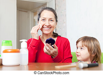 grandmother with granddaughter puts facepowder - Happy...