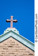 Cross on a stone church against a blue sky
