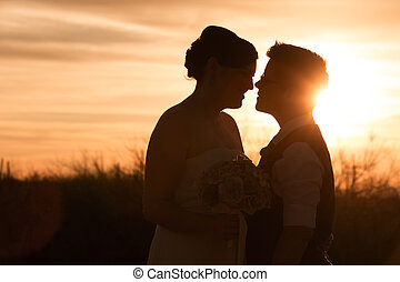 Lesbian Couple at Sunset - Beautiful same sex couple in...
