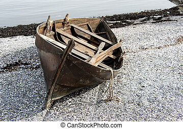 Rowboat on beach in Oslo - Abandoned old wooden row boat