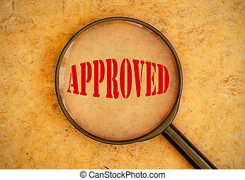 Approved - Magnifying glass focused on a stamp of approval