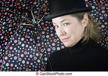 Woman in a bowler hat with umbrella