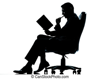 one caucasian business man sitting in armchair silhouette...