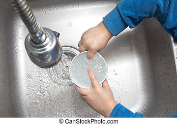 Boy doing the dishes in the sink