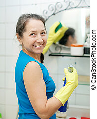 mature woman cleans mirror in bathroom at home