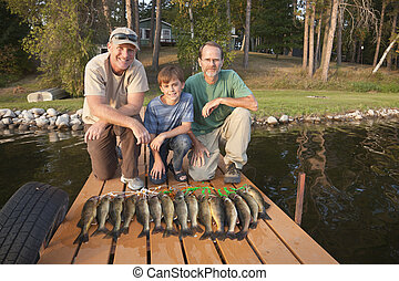 Two men and a boy posing with catch of fish - Two men and a...