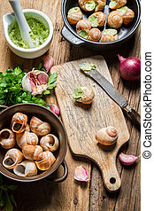 Preparing baked snails with garlic butter