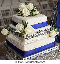 White Rose wedding cake with blue ribbons on silver plate