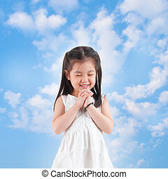 Praying - East Asian girl making a wish with smiling, blue...