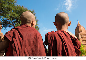 Rear view of two little monks standing under hot sun at...
