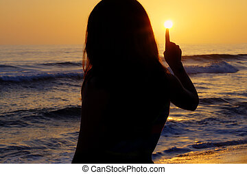 Touch the sun - Silhouette of young girl touching the sun...