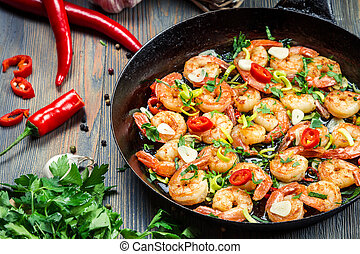 Freshly fried shrimps with herbs on old pan