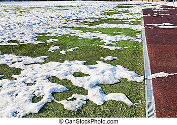 snowdrifts on outdoor soccer field in spring low season