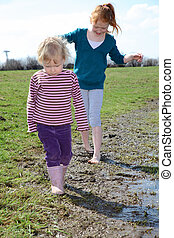 Muddy - Two kids walking trough a muddy puddle