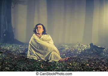 Woman in the misty dark old forest
