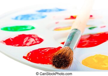 Artist's brush on a white palette with paints