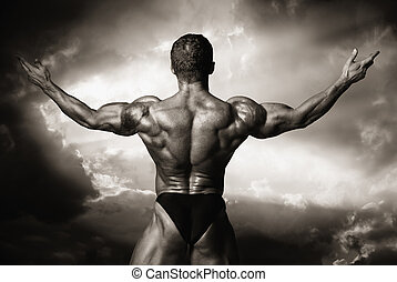 Man with his arms wide open outdoor against dark clouds.