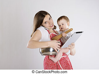 Mother and baby - Young mother is looking at tablet with her...