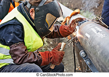 welding - Welder wearing protective clothing for welding...