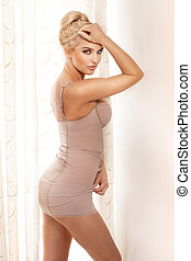 Photo of sexy sensitive woman looking at camera. Blonde wearing nude lingerie.