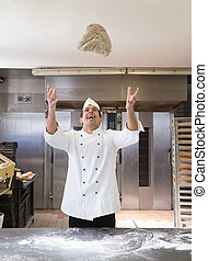 Baker throwing bread dough in bakery or bakehouse - Baker...