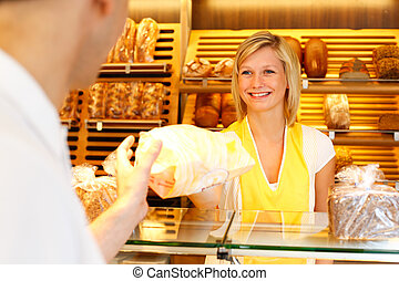 Baker's shop shopkeeper gives bread to customer - Bakery...