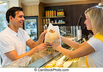 Shopkeeper giving pastry to customer - Bakery shopkeeper...