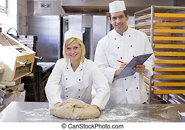 Instructor instructing an apprentice in bakery - Instructor...