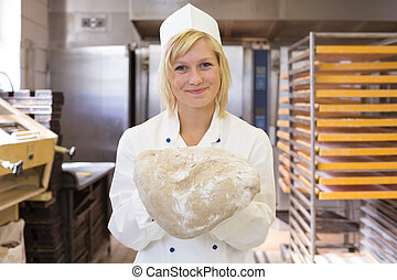 Baker with bread dough in bakery