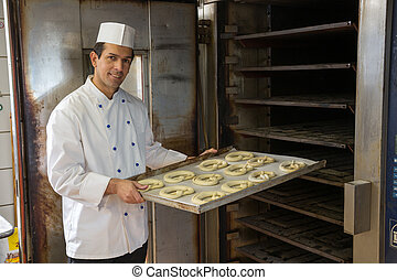 Baker putting pretzels into oven in a bakery - Baker puts a...