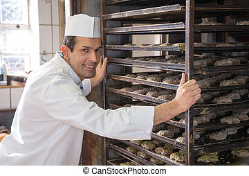 Baker putting a rack of bread into oven - Baker putting a...
