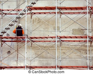 Worker on Scaffold - A construction worker is sitting on a...