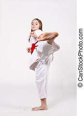 Kicking - Karate young girl in a kimono with a red belt...